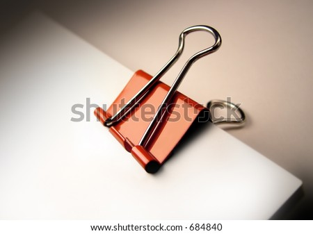 Red paper clip binding a stack of documents. - stock photo