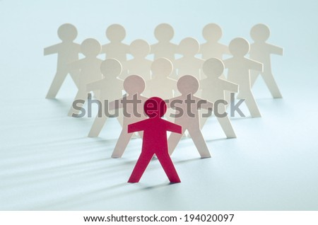 Red paper cut-out figure standing in front of other white paper cuts - stock photo