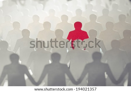 Red paper cut-out figure standing out among other white paper cuts - stock photo
