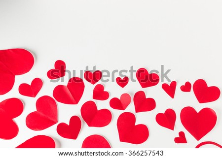 Red paper hearts made of Valentines Day confetti on white background with copy space. - stock photo