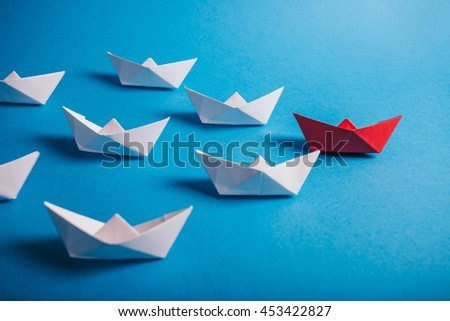 Red paper leader ship with fleet. Concept for leadership, management, motivation, difference and uniqueness. - stock photo