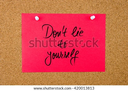 Red paper note with handwritten text Do Not Lie To Yourself pinned on cork board with white thumbtacks - stock photo