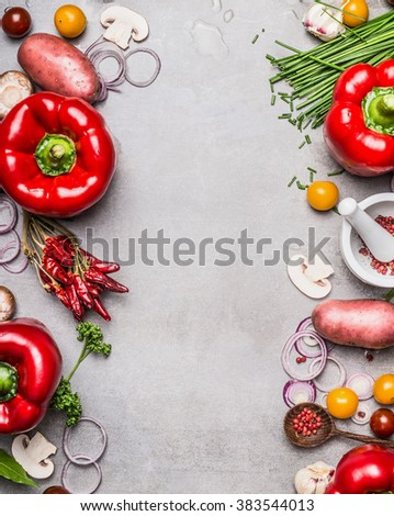 Red paprika and diverse vegetables and cooking ingredients on gray stone background, top view, frame, vertical. Vegetarian food and healthy lifestyle concept. - stock photo