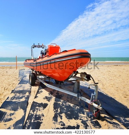 Red patrol lifeguard boat loaded on a trailer at the beach on a sunny day - stock photo
