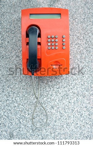 Red payphone on the wall - stock photo