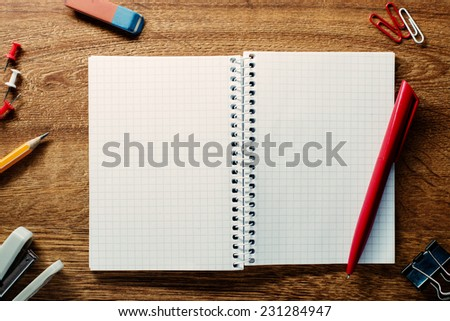Red pen ready for writing on an open spiral notebook with blank pages with math pattern surrounded by school supplies on a wooden table, high-angle close-up - stock photo