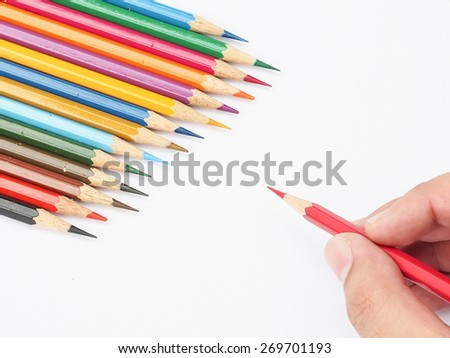 Red pencil holding on hand and blur multi-color pencil was background, Shallow in depth of field , Selective focus on sharpness of red color pencil  - stock photo