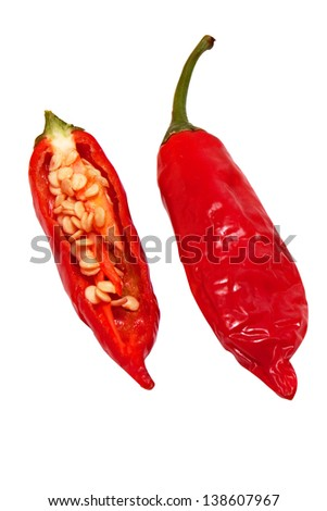 red pepper chili isolated on white background, one is cut to show the seeds - stock photo