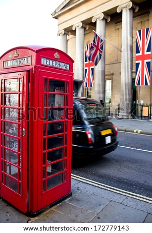 Red phone booth and local taxi in motion. London - stock photo