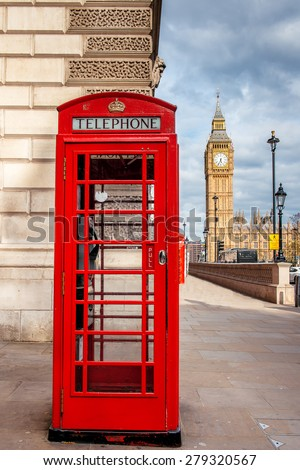 Red phone booth in London with Big Ben in the background - stock photo