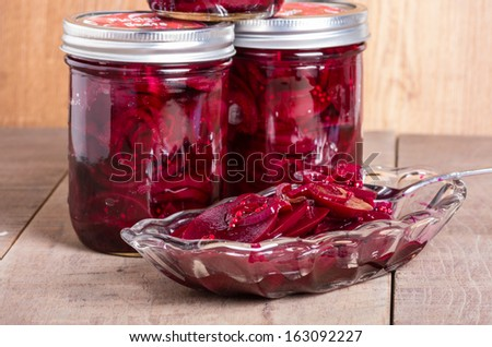 Red pickled beets in mason jars being served in a bowl - stock photo