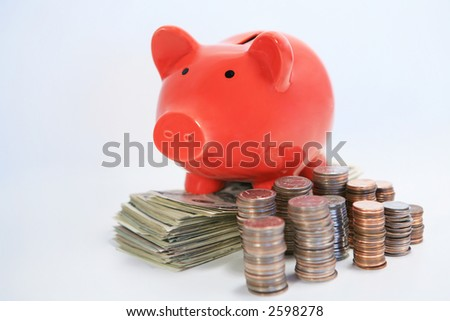 Red piggy bank on top of stacks of money coins and dollars side view - stock photo