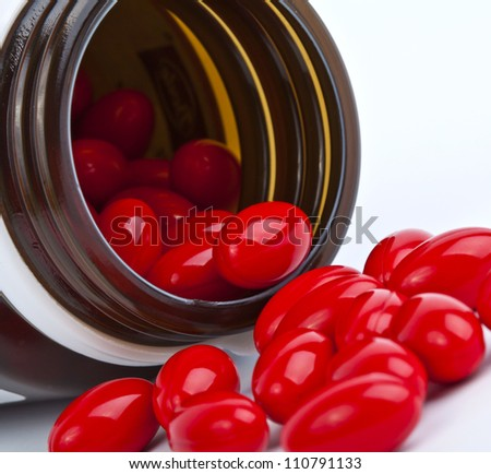 red pill in the bottle on white. - stock photo