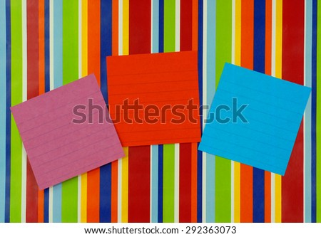 Red, pink and blue blank lined note pages pasted on a brightly colored striped background. The paper texture is visible. Copy space for message. Vivid, eye-catching colors ready for text. - stock photo