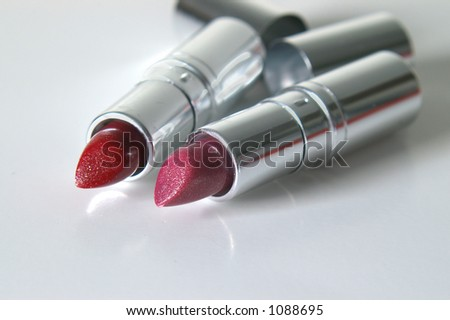 Red & pink glittery lipstick in silver tubes. - stock photo