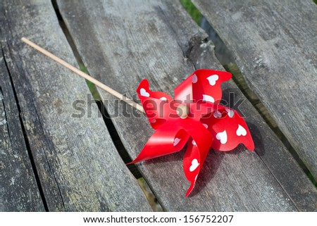 red pinwheel on wooden surface - stock photo