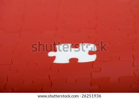 red plastic puzzle with one white piece - stock photo