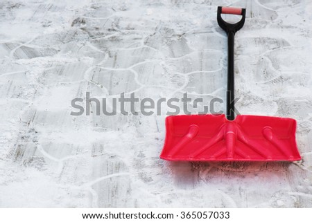 Red plastic shovel for snow removal. Winter is coming - stock photo