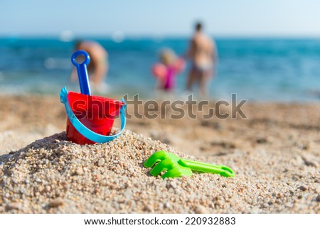 red plastic toy bucket and rake at the beach - stock photo