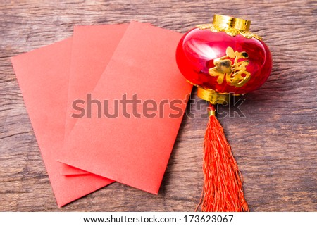 Red pocket and Chinese red lantern on wooden table top - stock photo