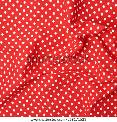 Red polka dot tablecloth or towel over the surface of a wooden table - stock photo
