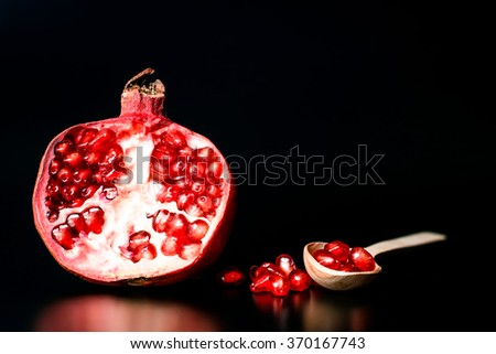 Red pomegranate fruit. Ripe vegetarian food. Sweet juicy fresh organic seed and spoon on black background. Healthy raw closeup tropical half piece with juice. Tasty dessert. Vintage effect - stock photo