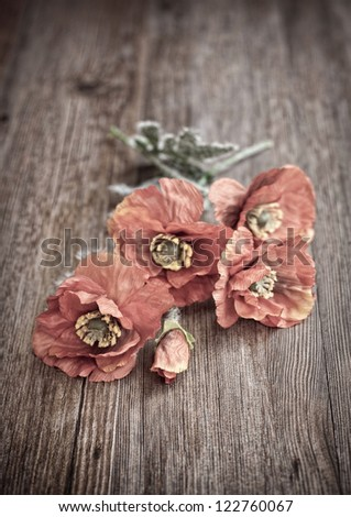 Red poppies on wooden table in vintage photo - stock photo