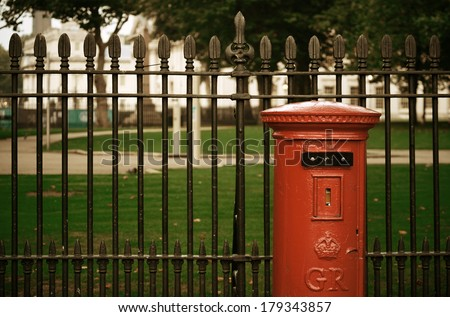 Red post box in street with historical architecture in London. - stock photo