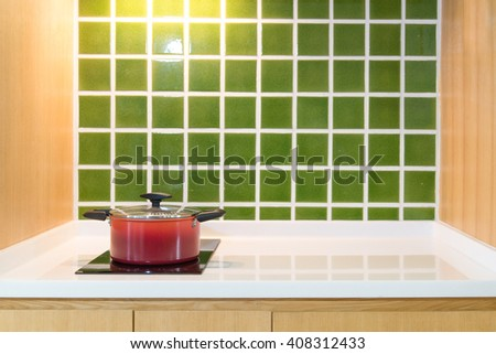 Red pot in the kitchen at home with green tile wall - stock photo