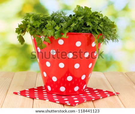 Red pot with parsley and dill on wooden table on natural background - stock photo