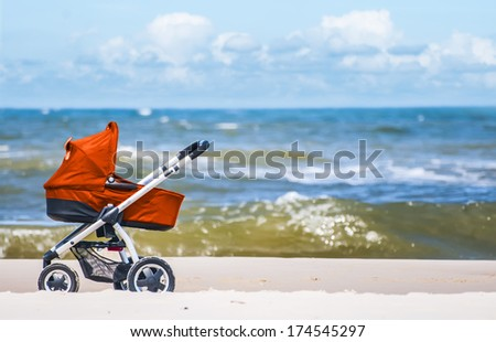 Red pram on a beach - stock photo