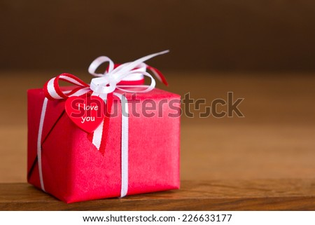 Red present with white bow and heart on dark wood, copy space, text, I love you - stock photo