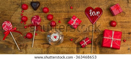 Red presents, candy, lollipops, chocolate, hearts on wooden table.Valentines decoration - stock photo