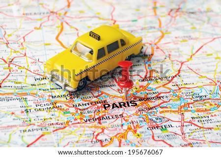 Red  push pin pointing at Paris , France and a taxi - stock photo