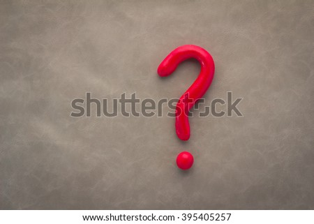 red question mark on grey leather background - stock photo
