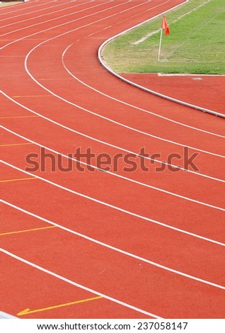red race running track rough texture white curve lines in the corner of a green grass sport field with a small red flag  - stock photo