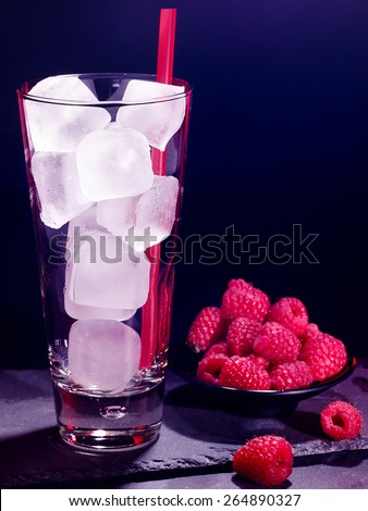 Red raspberry drink on black background. Empty glass with ice cube . - stock photo