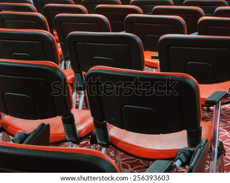 red recliners stand rows in an empty conference hall - stock photo