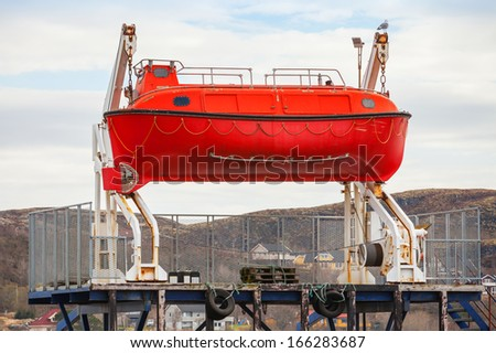 Red rescue boat stands on the coast in Norway - stock photo
