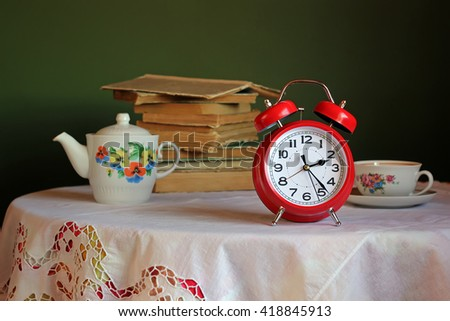 Red retro alarm clock on table with white tablecloth with lace. In the background a stack of books and an old teapot and teacup for tea. Retro still life with alarm clock. - stock photo