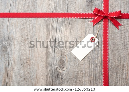 Red ribbon and bow with address label attached over wooden background - stock photo
