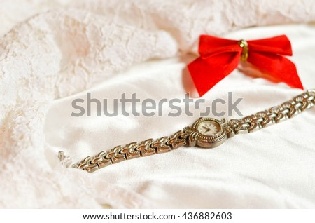 Red ribbon and hand watch laying on the wedding dress. Stylish and vintage background. - stock photo