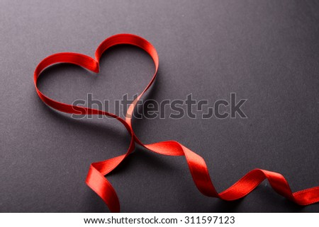 Red ribbon in shape of heart on gray background - stock photo