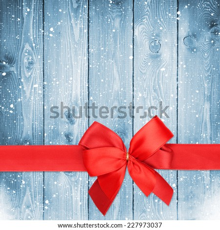 Red ribbon with bow over christmas snow wood background with copy space - stock photo