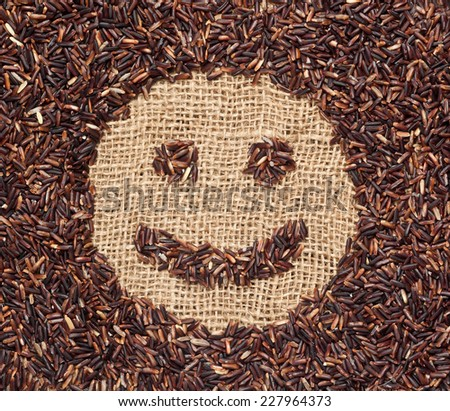 Red rice forming a smiley face on burlap fabric  - stock photo