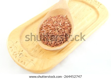 red rice in wooden spoon ware  - stock photo