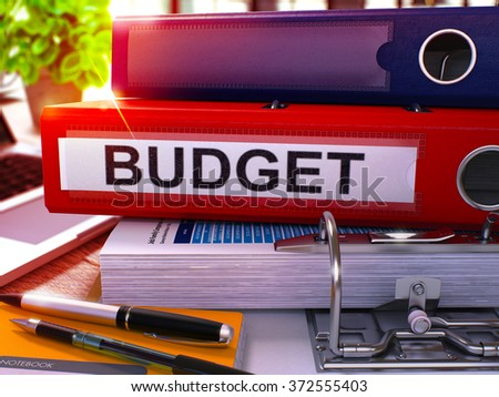 Red Ring Binder with Inscription Budget on Background of Working Table with Office Supplies and Laptop. Budget - Toned Illustration. Budget Business Concept on Blurred Background. 3D Render. - stock photo