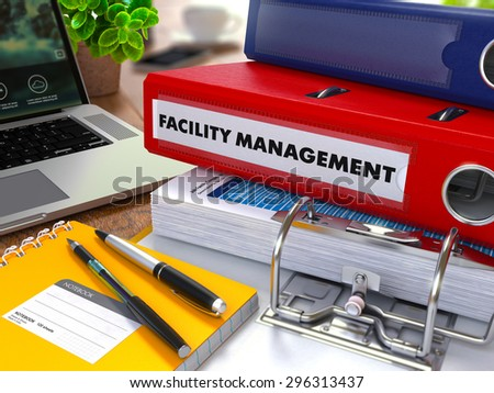 Red Ring Binder with Inscription Facility Management on Background of Working Table with Office Supplies, Laptop, Reports. Toned Illustration. Business Concept on Blurred Background. - stock photo