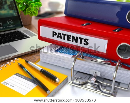 Red Ring Binder with Inscription Patents on Background of Working Table with Office Supplies, Laptop, Reports. Toned Illustration. Business Concept on Blurred Background. - stock photo