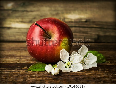 red ripe apple with blooming flowers on wooden - stock photo